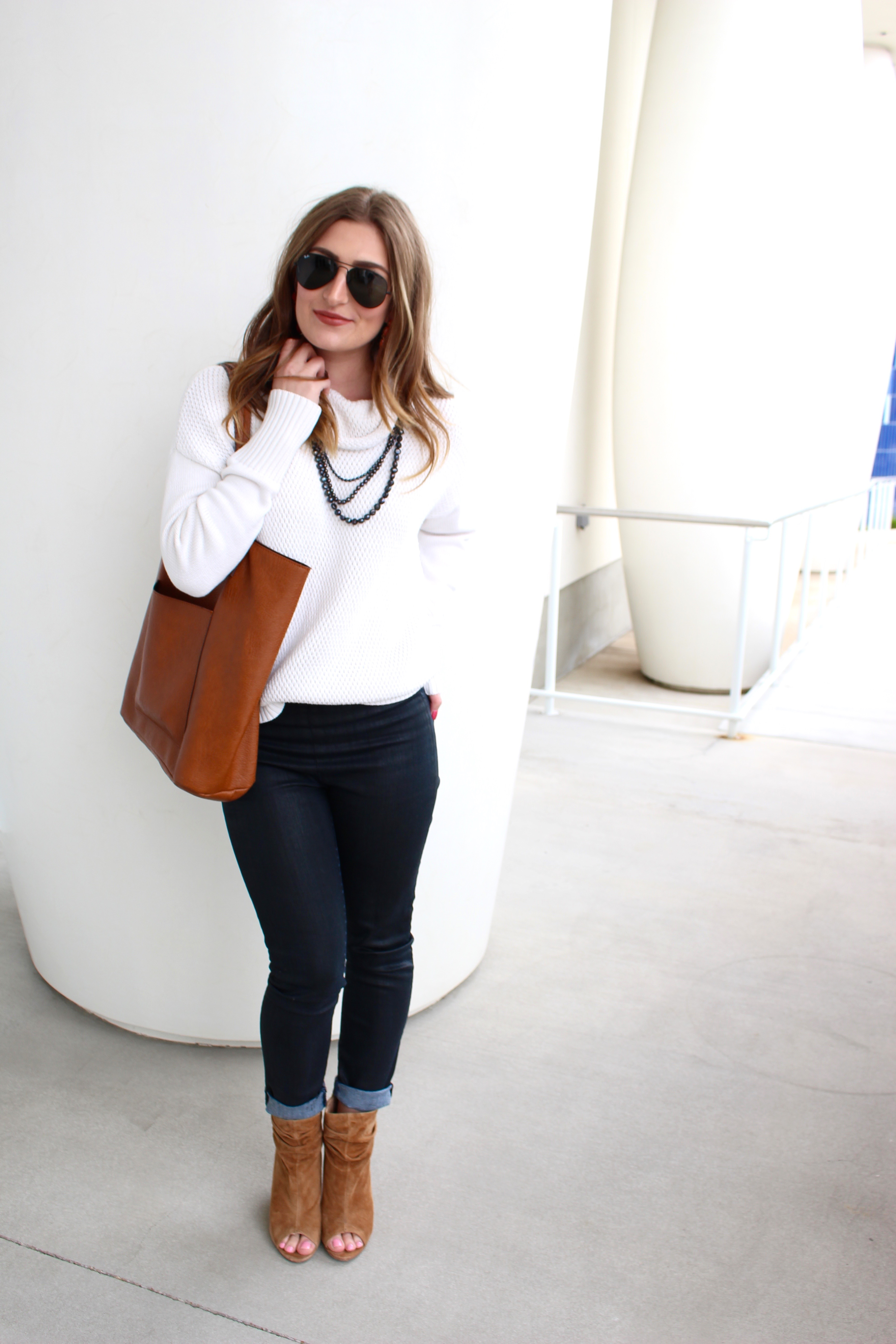 brown bag with a white turtleneck