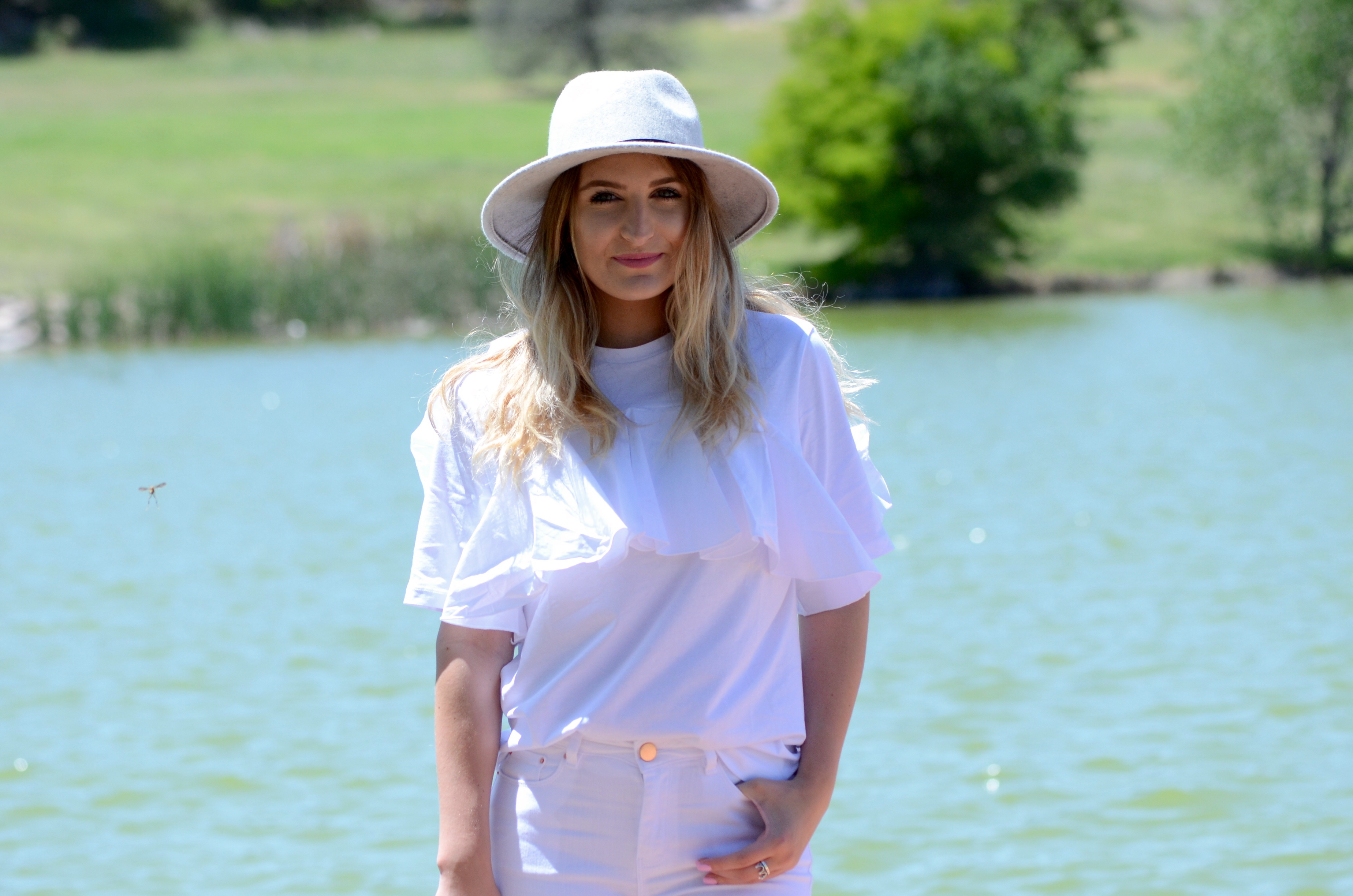 grey felt hat and an all white outfit
