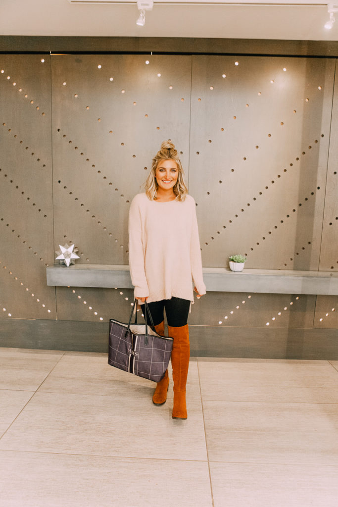 How To Style Leggings For Work featured by top US fashion blogger Audrey Madison Stowe; Image of a woman wearing a Red Dress over-sized sweater and OTK boots.