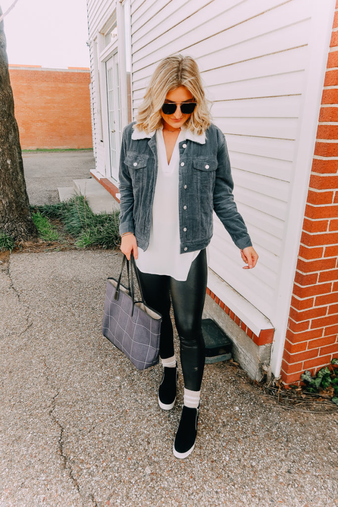Ways To Wear a White Blouse featured by top US fashion blogger Audrey Madison Stowe; Image of woman wearing white blouse, denim jacket, faux leather leggings and Steve Madden wedges.