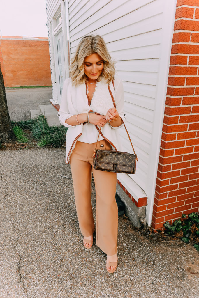 Ways To Wear a White Blouse featured by top US fashion blogger Audrey Madison Stowe; Image of woman wearing white blouse, shearling vest, work pants and nude heels.